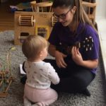 Baby interacting with key worker playing an instrument at Ashbourne Day Nurseries at Swanbourne