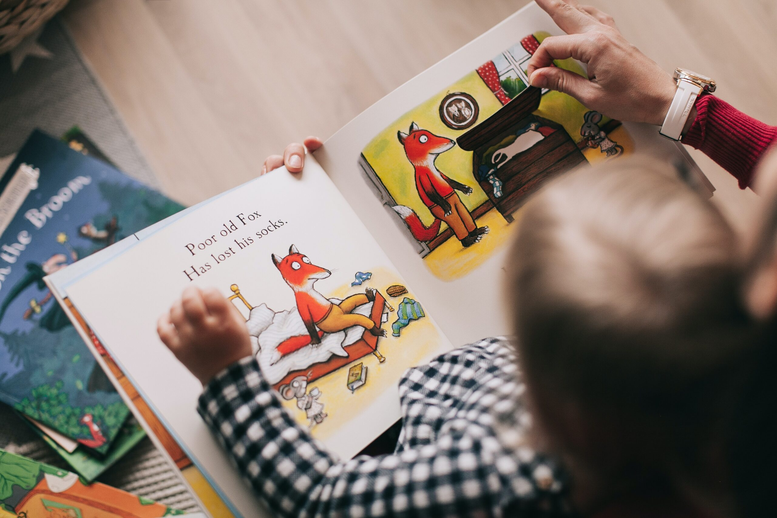 little boy reading a childrens book about fox with parent