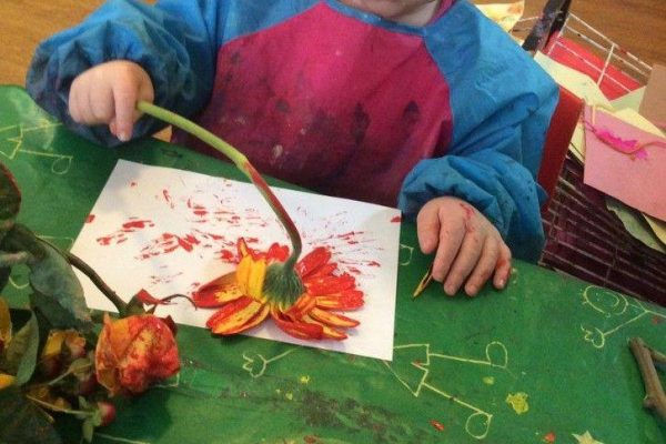 Child painting with flowers at Swanbourne nursery