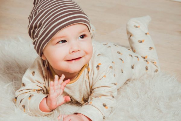 happy baby smiling with hand up, laying cute on a light rug